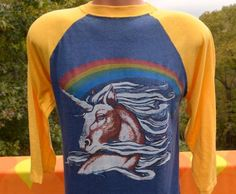 Tag: Teletrend copyright on graphicEra: 1984Fabric: 50 cotton 50 polySize reads: none, fits like modern adult MediumMeasures: 19 inches across the chest, 28 inches back collar to hemColors: navy blue and gold 3/4 sleeve raglan ringer t-shirt with rainbow UNICORN printCondition: great vintage shape - broken into perfection - soft and thin and lovelyFor reference, Magnum up there is 5-10.***