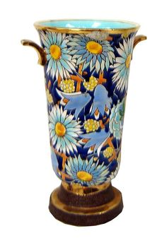 This Belgian Art Deco Floral Ceramic Vase is by Boch Freres, and features an overall pattern of daisies and blue bells against a grape arbor background.