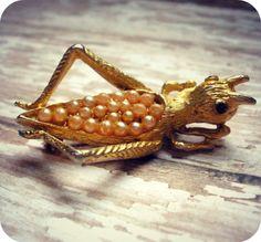 Vintage grasshopper brooch, signed BSK, gold tone and pearl. $12.00, via Etsy.