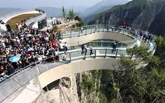 Visitors walk on the glass cantilever bridge on the cliff during the opening ceremony World's longest glass skywalk officially opens in Chongqing, China