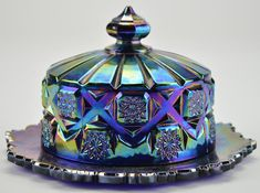 This Westmoreland lidded butter dish is a stunning collectible. It would also be beautiful as a part of your dining decor!  It is made of thick cut glass. The blue color is made even more vibrant by an iridescent Carnival glass finish. The slightly metallic shine makes this piece stand out. It features two parts: a circular dish and a deep lid.