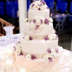 Fondant wedding cake decorated with white roses, purple lilac flowers and covered with lace.
