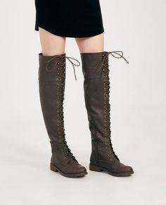 """<p>A pair of over-the-knee combat boots featuring a vegan leather upper anda lace-up front with metal grommets.</p>  <ul> <li>22"""" Shaft</li> <li>1.25"""" Heel</li> <li>17"""" Calf Circumference</li> <li>Zip Closure</li> <li>Lightly Padded Footbed</li> <li>Tread Sole</li> <li>Man Made Materials / Metal</li> <li>Imported</li> </ul>"""