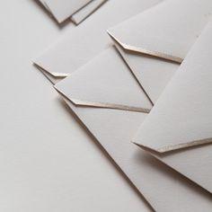 Dove-gray envelopes with metallic edges.