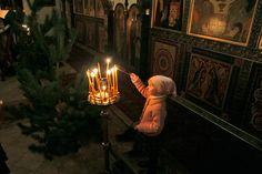 A girl lights a candle during Christmas night Divine Liturgy at the church of Three Prelates in Moscow