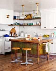 The weathered wood top and rusty green base give the all-white, freshly renovated kitchen more personality.