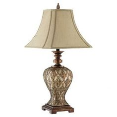 "Table lamp with raised diamond and floral motifs.  Product: Table lamp    Construction Material: Resin and fabric    Color: Gold, silver and coppery metallic     Features:   Stair step footed platform base   Raise diamond and leaf carvings   Cream cut corner fabric shade  Accommodates: (1) Bulb - not included    Dimensions: 30.5"" H x 15"" W x 15"" D"