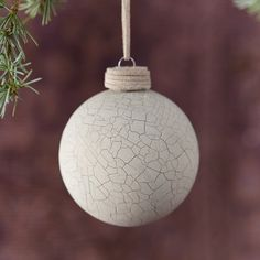 """A crackled finish tops this matte glass globe ornament.- Glass, ribbon- Indoor use only- Hanging loop: 2.5""""- Imported3.8""""H, 3.25"""" diameter"""