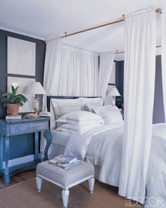 In the master bedroom of Geoffrey Ross and John Dransfield's Hamptons weekend house, the bed, canopy rail, European shams, and duvet cover are all by Dransfield and Ross. The nightstands are galvanized-steel American Empire pier tables, and the walls are painted in Benjamin Moore's Kendall Charcoal.