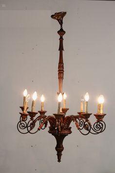 Lampadario del 900. Corpo in legno e bracci in ferro battuto e foglie intagliate in legno. Dieci bracci e punti luce.