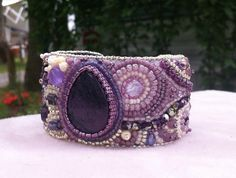 A OOAK bead embroidered cuff. My entry for the Etsy Bead Embroidery Guild Mini Beadfest Purple. I used a purple teardrop shaped focal bead and accented with various sized purple, cream, white and silver beads. It is backed with blue ultra suede. I am a proud member of the Etsy Bead Embroidery Guild.