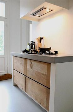 Kitchen in white, with wood and concrete.
