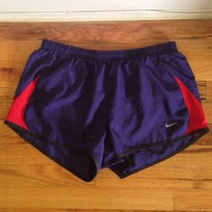 Nike Dri Fit Running Shorts Blue & Red Nike Dri Fit running shorts. Dark blue base color and red sides with black lining. Built in interior underwear with a small interior pocket. Excellent condition just a little lint stuck on from the dryer after washing them! Size L. Nike Shorts