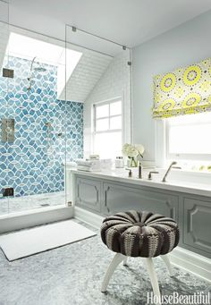 The circular motif of Ann Sacks's Beau Monde Glass Mosaics tile in this San Francisco master bathroom is echoed by a round stool found on Etsy and a Roman shade in Schumacher's Soleil L.A. Print. Bath and shower fixtures are by Waterworks, while the tub surround is from Caesarstone.   - HouseBeautiful.com