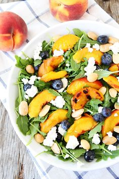 For the Dressing: 4 tablespoons olive oil 2 tablespoons white or golden balsamic vinegar 1 teaspoon honey Sea salt and crushed black pepper, to taste  For the Salad: 3 ripe peaches, cut in half, pits removed Fresh arugula (about 8-10 cups) 1 cup fresh blueberries 1/3 cup Marcona almonds or regular almonds 2 oz fresh goat cheese.