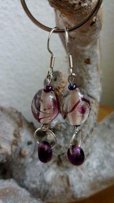 Transparante kraal met paarse strepen  (handgemaakt), met daaraan een ringetje met paarse druppelkraal. VERKOCHT