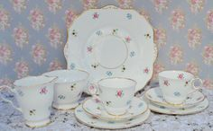 Vintage bone china tea set for two made by Royal Stafford, likely manufacture date 1940s - 1950s. The tea set consists of milk jug, sugar bowl, serving plate for cakes or sandwiches and a pair of tea cups, saucers, tea plates. The china is white and feature a pattern of tiny ditsy flowers in multi colours - pansies, roses, forget-me-nots. The china is gilded to the feet of the jug, cups and bowl with further gilding to the jug and cup handles and a scroll design in gilt on the tab handles of…
