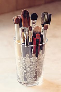 Store makeup brushes in a tumbler filled with tiny glass stones. Great idea... they sell the little stones at wally world.
