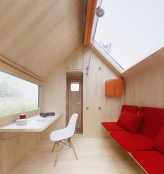The small dwelling sports a living area, with folding desk and chair, a sofa bed and kitch...