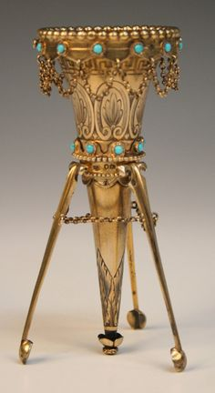 A Victorian silver gilt posy holder of conical form with beaded rim above a band of turquoise beads, hung with chain decoration, the body engraved with Greek key and anthemion borders above another band of turquoise beads, on hinged tripod legs united by a chain, London, 1872.