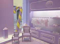 Larger then life candy canes,baroque style chairs, lilac/white interior with the brands signature Medusa head on the walls and carpet.