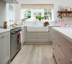 cuisine equipee avec meuble bas gris et lavabo blanc, ilot central rose, parquet clair, poele inox et etageres ouvertes en bois et metal