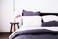 Linen bedding with stool as nightstand