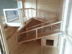 Inside a rabbit shed, has a shelf with ramps and a built in hideout for the rabbits under the ramps.: