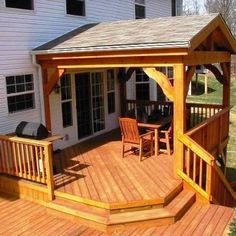 This gorgeous second story porch and deck features cedar wrapped columns, roof beam and railings with pressure treated pine decking.  Note the curved bracing on porch.