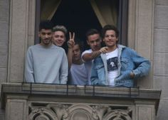 The boys waving to fans from their hotel balcony in Milan, Italy.