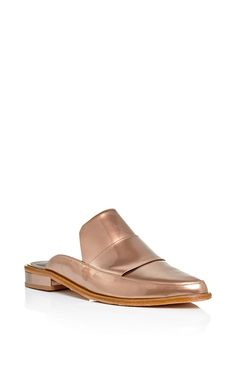 Amy Smilovic enhances her minimalist signature style with global influences, fusing sculptural modernity with wanderlust inspirations. For Fall 2015 she delivers these **Tibi** Denni slip on loafers in bronze leather, crafted with a slight heel.