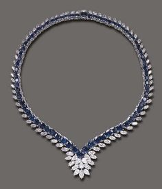 A SAPPHIRE AND DIAMOND NECKLACE   Of flexible V-shaped design, the graduated cushion-cut sapphire line, enhanced by marquise-cut diamond trim, the front accented by pear and marquise-cut diamond cluster detail, mounted in 18k white gold, 15¼ ins.