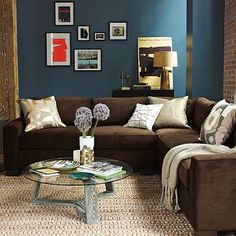 I love the colors in this room. The rich blue and the cozy brown couch. Despite the darker colors, the room's accents keep it light. I would LOVE this couch!