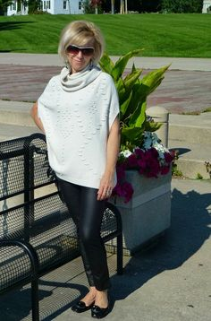 Ela in her wite knit poncho with black leggings.