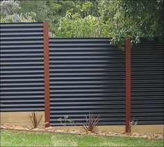 Contemporary Landscape/Yard with Corrugated fence with wood to create supports and ledges, Fence