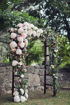 Stunning wedding arch with white hydrangeas and pink garden roses. Learn how to get your own with our pointers. | http://www.weddingpartyapp.com/blog/2014/10/22/stunning-wedding-arches-diy-buy/#more-31856