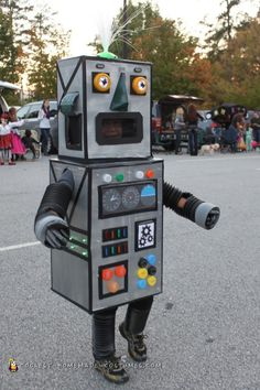 """We can't leave the boys out of the light-up fun! This DIY robot costume takes the time-tested cardboard box classic and adds some high tech features with battery operated lights, reflectors, and even a fiber-optic wand for """"hair.""""  See more at Coolest Homemade Costumes."""