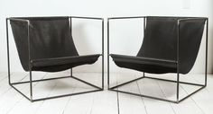 Pair of leather slinged chairs with iron cubed frame.