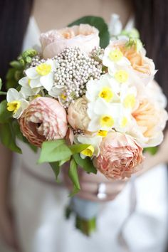 A pink bouquet with garden roses, daffodils, and rice flowers | Brides.com
