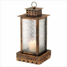 Kyoto Candle Lantern  Lacy filigree trim and ornate pressed glass panels are a striking counterpoint to the slender, squared shape of this elegant bronze-finish lantern. A glowing example of balance and form!