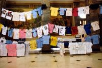 "Crime Victims Week Clothesline Project in the Bronx County Building Rotunda.  The display features t-shirts decorated by children and adults traumatized by rape, child abuse, gun violence and other misfortune. The artwork educates the public and helps victims heal.  ""I miss my two brothers. They died in the streets,"" reads a wrinkled white t-shirt with glitter glue writing.   From NY Daily News."