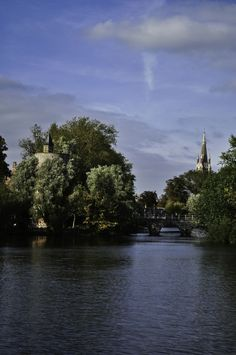Lake in Bruges, Belgium, with bridge to the medieval city gate, and tower of church