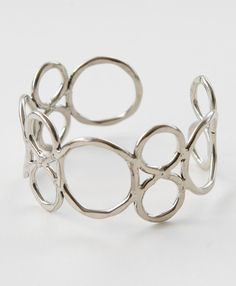 Rings of hammered brass coated in luminous sterling silver loop around your wrist in this classic accessory.