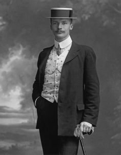 A young man poses for a portrait in a suit, worn with a waistcoat and straw boater, circa 1905. The picture was taken by photographer Henry Mayson (1845 - 1921) at his studio in Keswick in the Lake District.