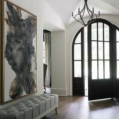 A black arched front door complemented with arched sidelights provides a bit of drama to a chic foyer lit by a quatrefoil light pendant and boasting a large gold and gray abstract art piece hung over a gray linen tufted bench placed on a wood herringbone Arched Front Door, Front Door Entryway, Grey Front Doors, Entrance Foyer, Entry Doors, Entryway Decor, Entryway Ideas, Front Entry, Grand Entryway