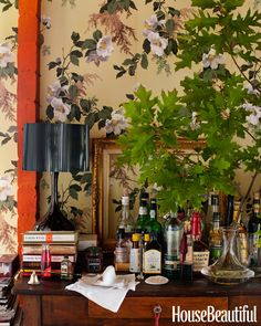 In the dining room of their Barnard, Vermont, cottage, Deirdre Heekin and Caleb Barber set up a sumptuous old-world bar on her childhood desk, placed against a backdrop of vintage wallpaper from Second Hand Rose.