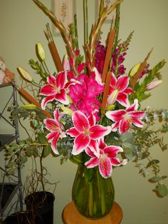 Upscale lily arrangement by Texas Blooms. Florals include stargazer lilies, burgundy snapdragons, fuchsia gladiolas, cattails, horsetail reed and eucalyptus.