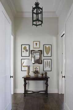 James Michael Howard    Beautiful foyer entrance.Soft gray paint wall color. Antique wood console table, photo gallery with wood frames, mirror, wood lamp, wood floors and black pendant light! gray brown black entrance entry foyer colors.