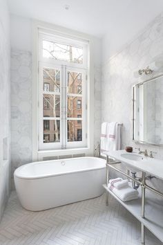 A free standing oval tub by Waterworks sits under a double casement window framed by white marble hex backsplash tiles and white upper walls in this beautifully appointed bathroom featuring white marble herringbone bathroom floor tiles positioned beneath a Waterworks nickel and marble double washstand place below a polished nickel mirror lit by a 2 light nickel sconce.