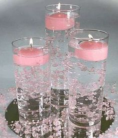 Simple floating candle, water candle, centerpiece adds elegance to an evening wedding. They are inexpensive and easy as a DIY project. Vases available from the dollar store or local craft shop. Use your favorite flowers in the water, babies breath, or water pearls. Match the floating candles to the colors of your event. Our floating candles are available in many sizes, square and round, in many wonderful colors. For a real punch of color try our floating gel candles! www.BeverlyHillsCandle.c...